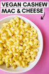 "bowl of cashew mac and cheese with a text overlay that reads ""vegan cashew mac & cheese"" with an arrow pointing toward the bowl"