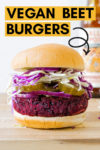 """forward shot of a vegan beet burger topped with pickles, onion and cabbage with a beer in the background and a text overlay that reads """"vegan beet burgers"""" and an arrow pointing toward the burger"""