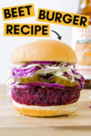 """forward shot of a vegan beet burger topped with pickles, onion and cabbage with a beer in the background and a text overlay that reads """"beet burger recipe"""" and an arrow pointing toward the burger"""