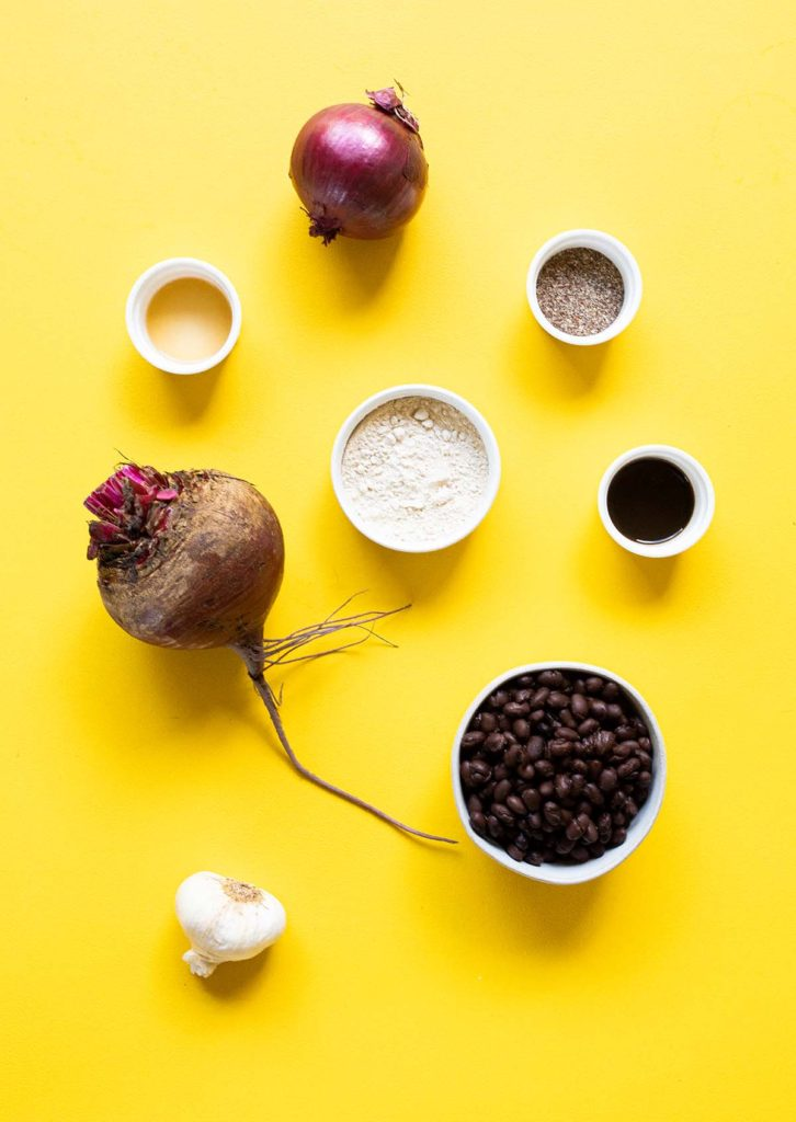 ingredient spread to make vegan beet burgers which includes a beet, a red onion, black beans, vital wheat gluten, worcestershire, garlic, and flax meal