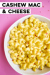 "bowl of cashew mac and cheese on a pink background with text overlay that reads ""cashew mac & cheese"""
