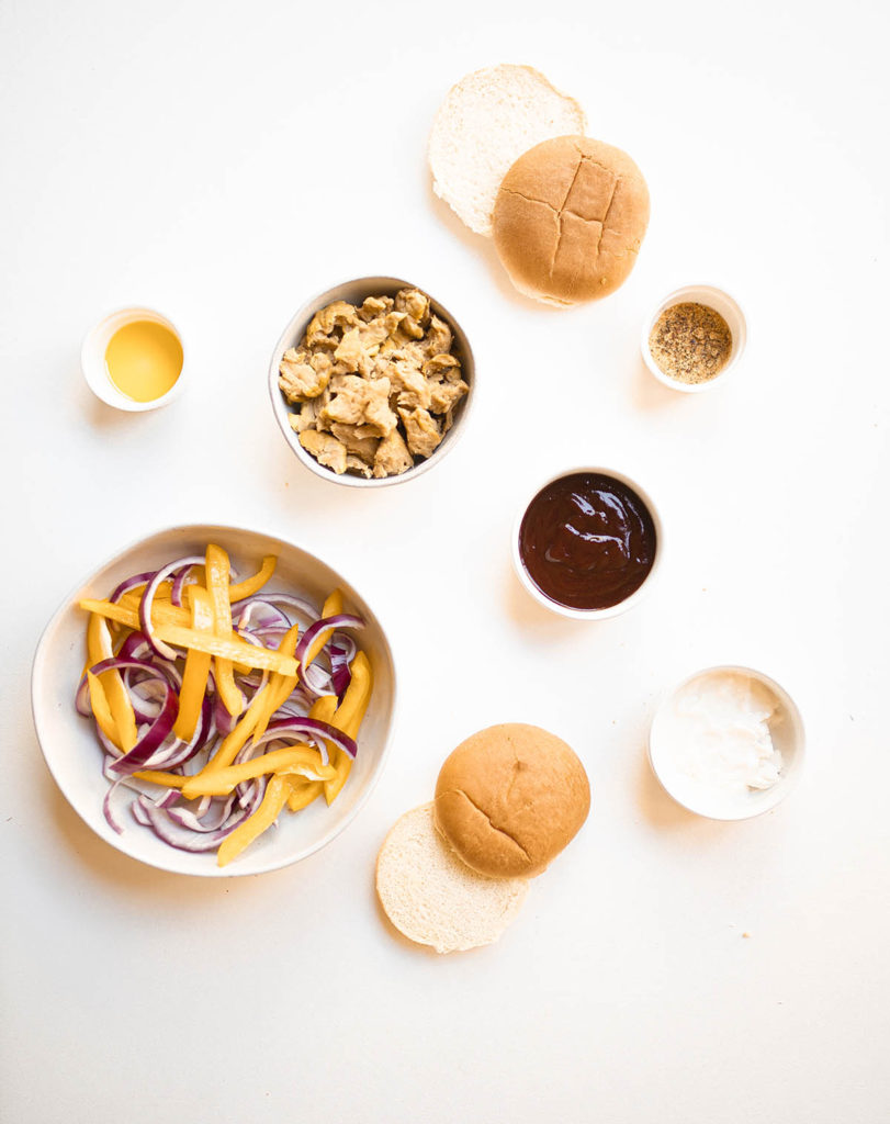 ingredients to make bbq chicken sandwiches on a white background - two buns, vegan mayo, peppers, onions, bbq sauce, olive oil, fajita seasoning, and chicken seitan