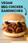 """bbq chicken sandwich on a cutting board against a blue background with chips on the side with a text overlay that reads """"vegan bbq chicken sandwiches"""" and an arrow pointing to the sandwich"""