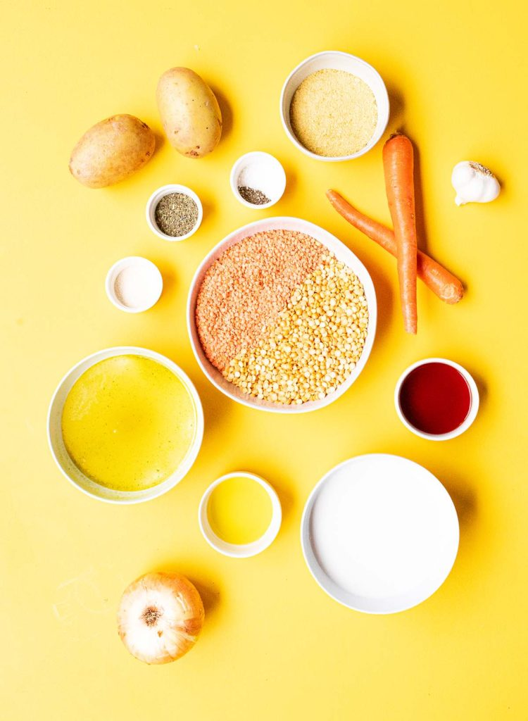 ingredients spread of red lentils, yellow split peas, potatoes, carrots, vegetable broth, nutritional yeast, garlic, spices, red wine vinegar, coconut milk, extra virgin olive oil, and an onion against a bright yellow background