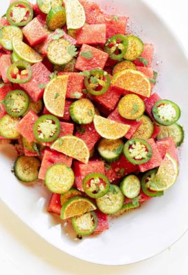chili lime watermelon cucumber salad on a large plate on a white background