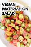 "plate of chili lime watermelon cucumber salad with a text overlay that reads ""vegan watermelon salad"""