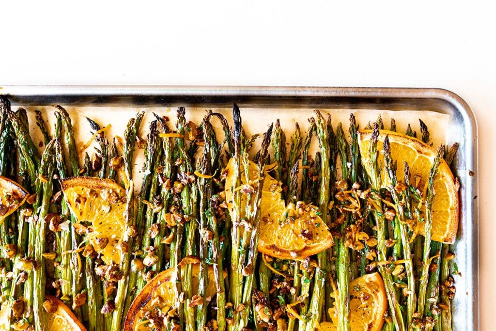 oven-roasted asparagus displayed vertically with citrus, thyme, and pistachio on a baking sheet against a white background