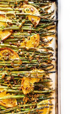 oven roasted asparagus displayed horizontally with citrus, thyme, and pistachio on a baking sheet with parchment paper on a white background