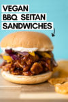"""bbq chicken sandwich with chips on the side and a text overlay that reads """"vegan bbq seitan sandwiches"""" and an arrow pointing toward to the sandwich"""