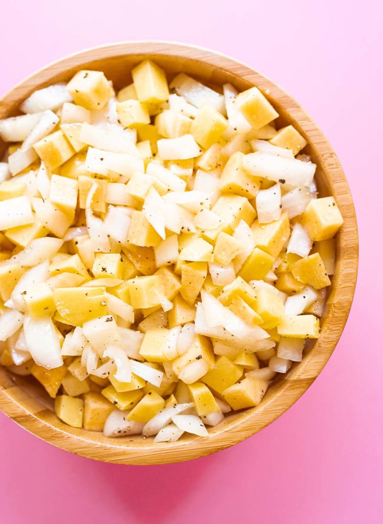 a bowl of chopped rutabaga, potato, and onion against a pink background