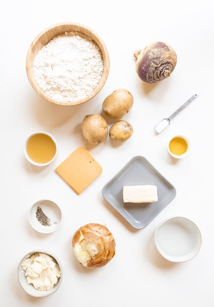 Cheese and onion Cornish pasty ingredients spread out on a white background