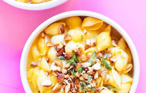 two bowls of butternut squash pasta on a pink background