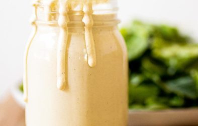jar on a wooden board filled with cashew caesar dressing with some of the dressing dripping over the edge and a green salad in the background