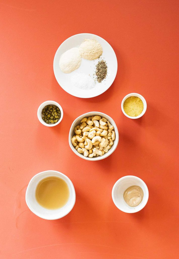 ingredient spread for cashew caesar dressing featuring cashews, dijon mustard, lemon juice, nutritional yeast, capers, and spices on a red background