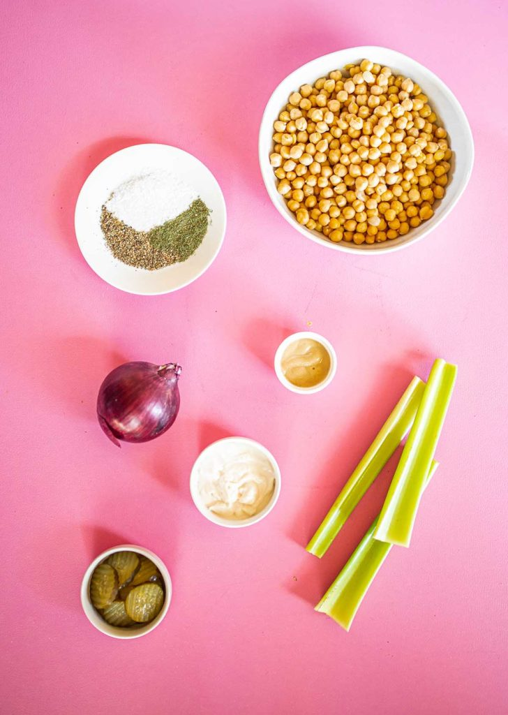 ingredient spread for chickpea salad including chickpeas, celery, red onion, pickles, spices, vegan mayo, and dijon