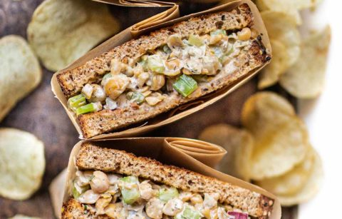 array of four chickpea salad sandwich halves wrapped in parchment paper on a baking sheet with potato chips scattered about