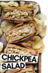 """array of four chickpea salad sandwich halves wrapped in parchment paper on a baking sheet with potato chips scattered about with a text overlay that reads """"chickpea salad"""""""