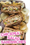 """array of four chickpea salad sandwich halves wrapped in parchment paper on a baking sheet with potato chips scattered about with a text overlay that reads """"chickpea salad sandwiches"""""""