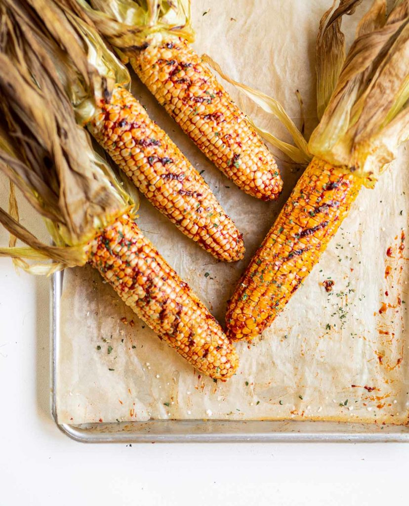 four ears of roasted corn coated in agave chipotle sauce staggered on a baking sheet