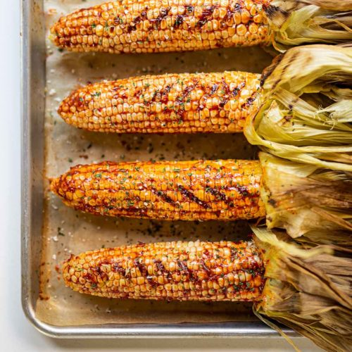 four ears of chipotle sweet corn on a baking sheet