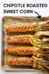 "four ears of chipotle sweet corn on a baking sheet with a text overlay that reads ""chipotle sweet corn"" and an arrow pointing to the corn"