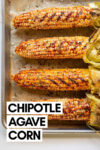 """chipotle roasted sweet corn on a baking sheet with a text overlay that reads """"chipotle agave corn"""""""