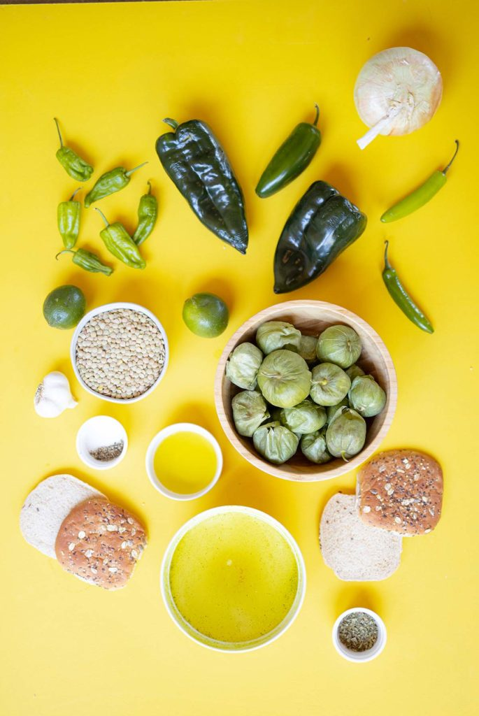 ingredient spread for green chili lentil sloppy joes featuring tomatillos, serrano peppers, jalapeño peppers, padrón peppers, limes, lentils, vegetable broth, olive oil, pasilla peppers, limes, buns, vegetable broth, garlic, mexican oregano and salt and pepper.