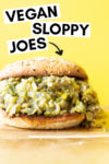 "forward shot of a green chili lentil sloppy joe with a text overlay that reads ""vegan sloppy joes"" with an arrow pointing toward the sandwich"