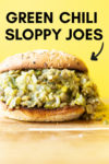 "forward shot of a green chili lentil sloppy joe with a text overlay that reads ""green chili sloppy joes"" with an arrow pointing toward the sandwich"