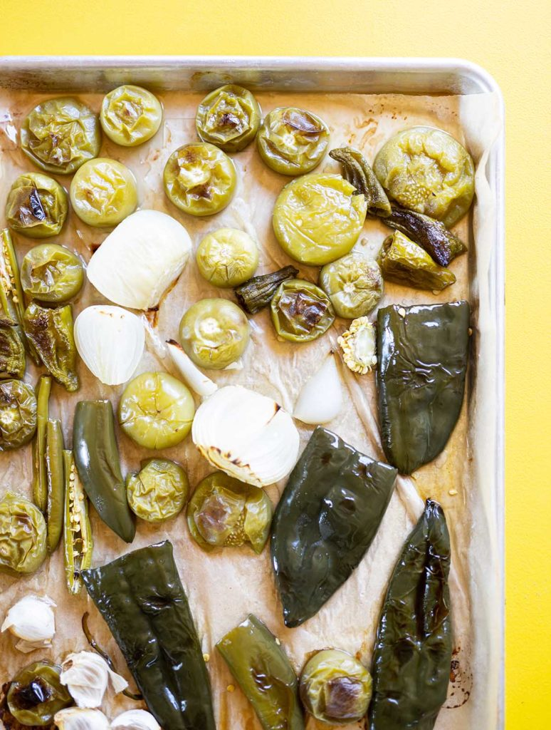 roasted tomatillos, onions, garlic, and peppers on a baking sheet against a bright yellow background