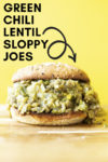 "forward shot of a green chili lentil sloppy joe sandwich on a wood cutting board with a yellow backdrop and a text overlay that reads ""green chili lentil sloppy joes"" with an arrow pointing to the sandwich"