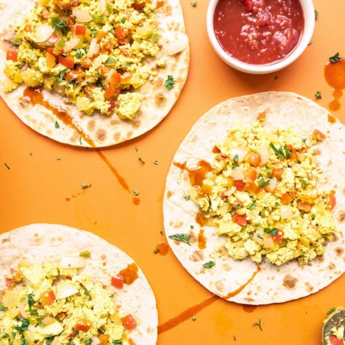 array of vegan breakfast tacos on an orange background topped with parsley flakes and hot sauce drops served with a side of salsa