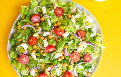 vegan caesar salad on a yellow background with a side of cashew caesar dressing and a few stray crispy chickpeas