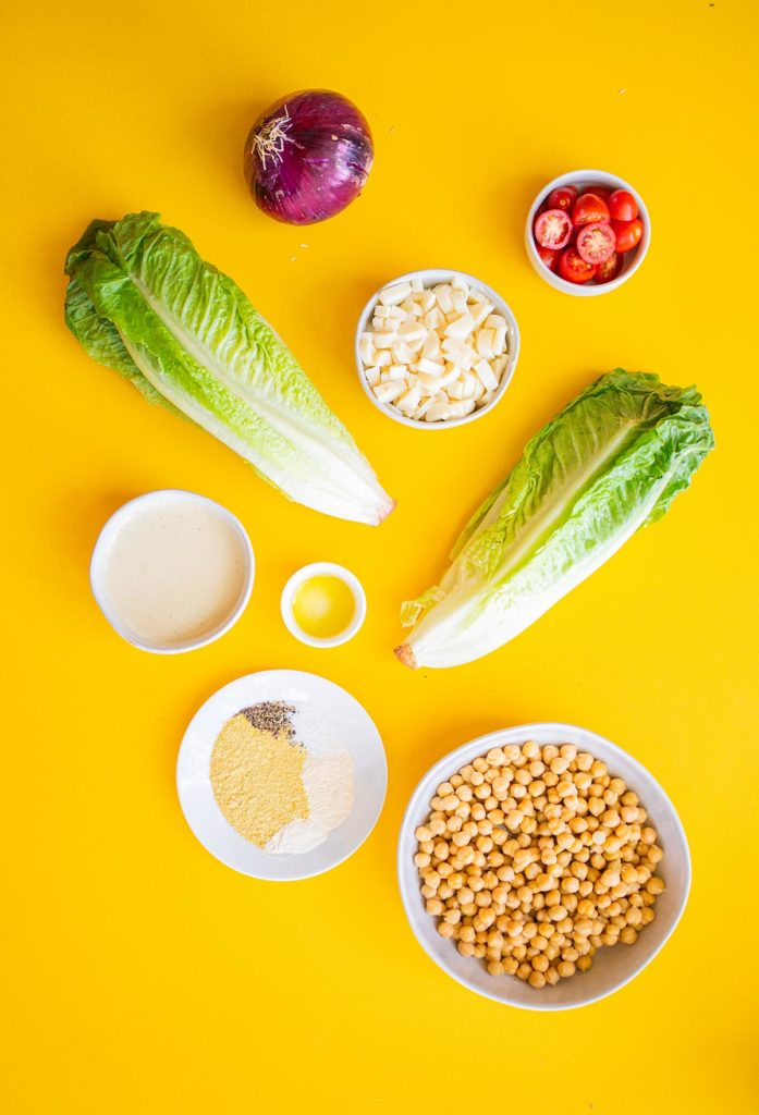 ingredient spread of romaine hearts, cashew caesar dressing, chickpeas, spices, olive oil, hearts of palm, red onion and grape tomatoes