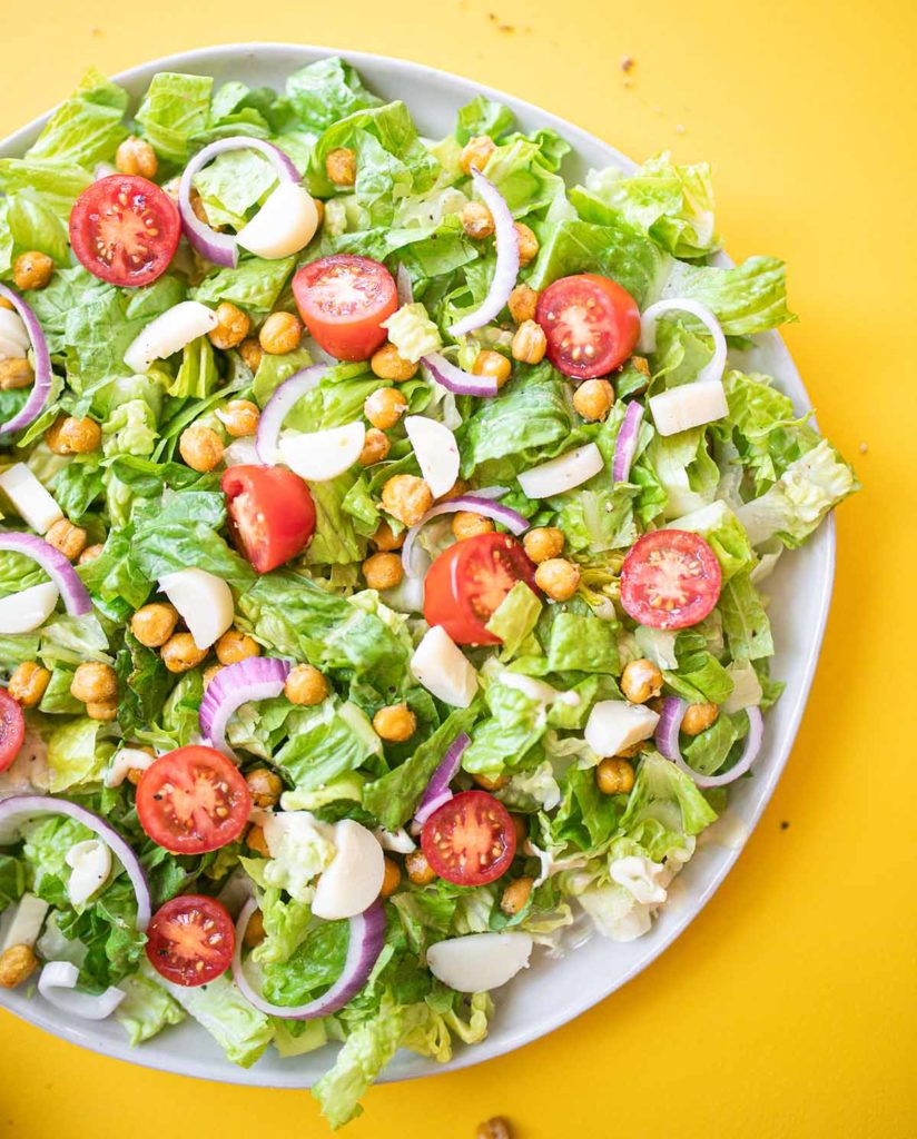 cashew caesar salad on a plate surrounded by stray crispy chickpeas