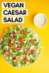 """vegan caesar salad with crunchy chickpeas and a side of caesar dressing with a text overlay that reads """"vegan caesar salad"""""""
