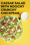 """vegan caesar salad on a yellow background with a side of cashew caesar dressing and a few stray crispy chickpeas and a text overlay that reads """"vegan caesar salad with noochy crunchy chickpeas"""" and an arrow pointing toward the salad"""