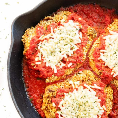 vegan chicken parmesan in a skillet on a white background