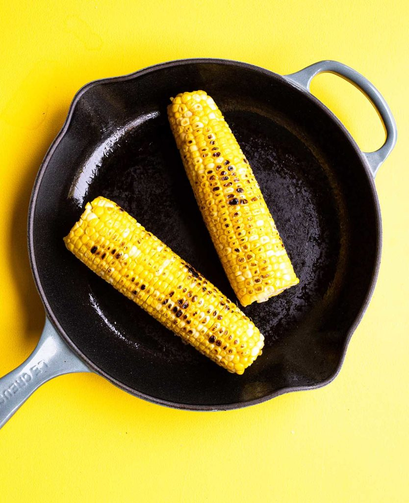 two ears of charred corn in a skillet