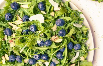 two arugula blueberry salads with a side of coconut poppyseed dressing