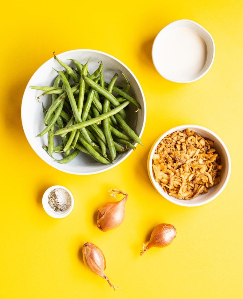 overhead shot of double onion green beans ingredients: a bowl of oat milk, green beans, fried onions, a few shallots and some salt and pepper