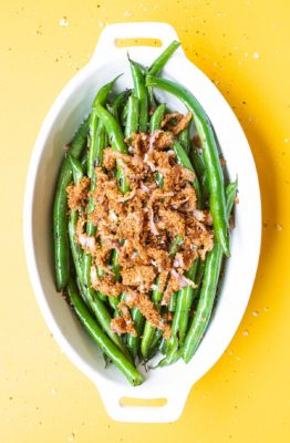 overhead shot of small casserole dish of double onion green beans on a yellow background with salt and pepper flakes