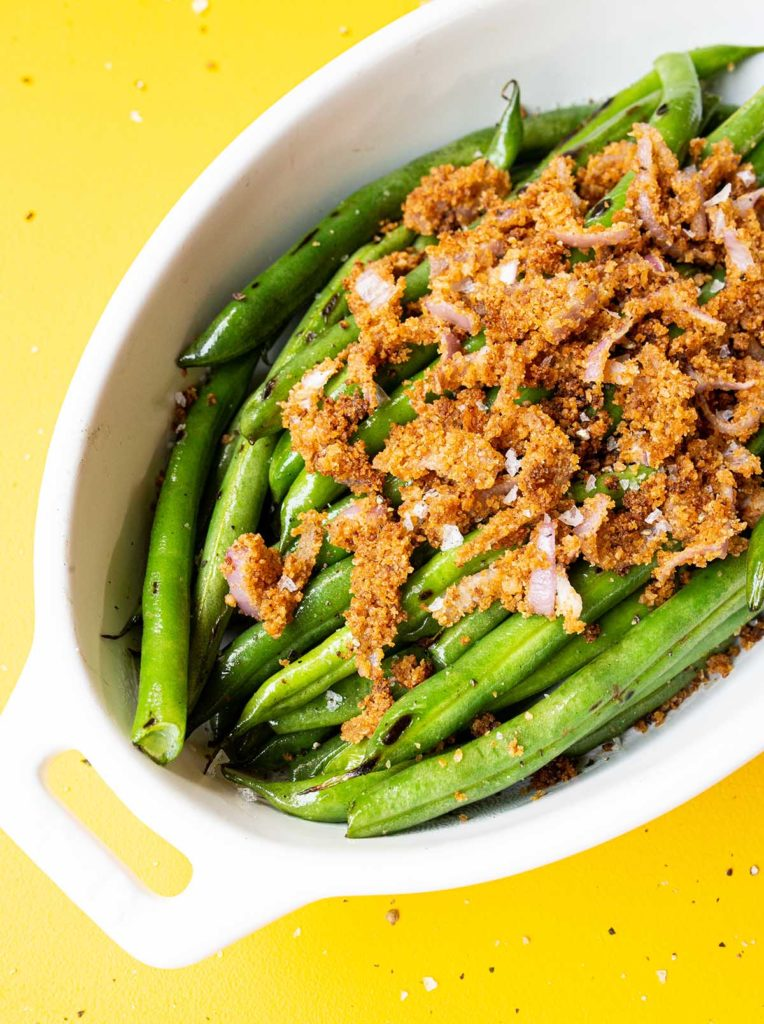 45 degree angle shot of small casserole dish of double onion green beans on a yellow background with salt and pepper flakes