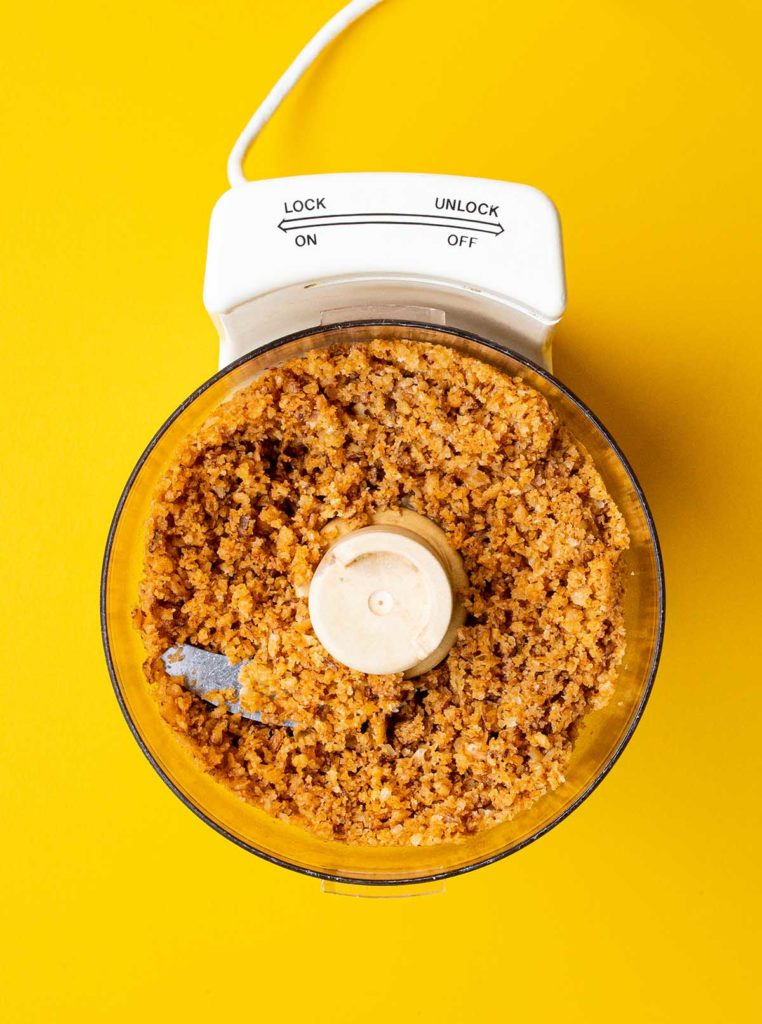 overhead shot of a food processor with the top off filled with pulverized  fried onions