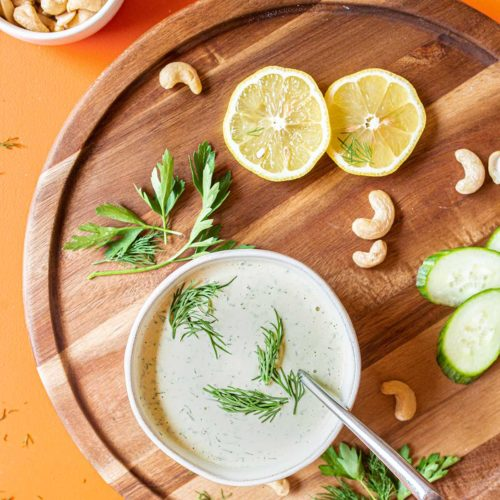 a bowl of parsley and dill salad dressing on a wooden tray surrounded by lemons, cucumbers, herbs and raw cashews
