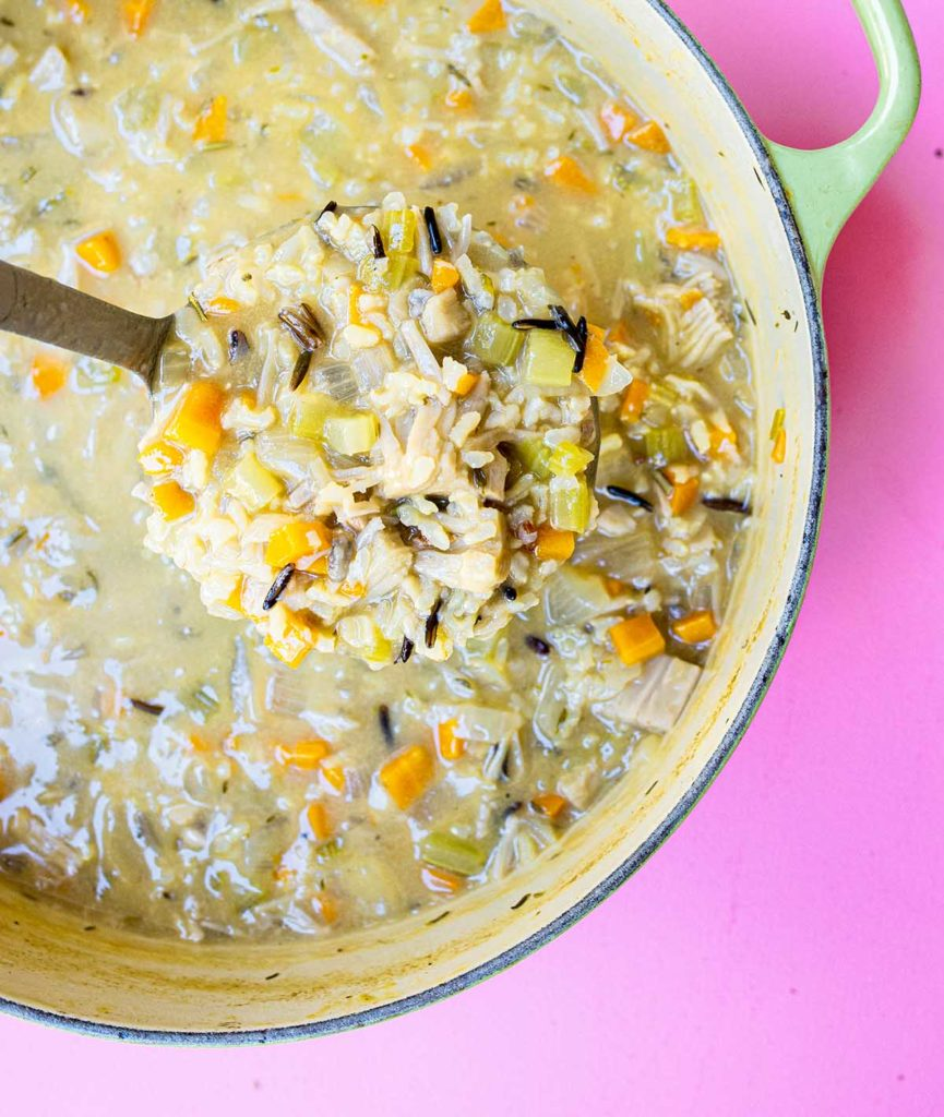 dutch oven filled with vegan wild rice soup with a ladle full of soup.