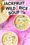 """two bowls of vegan wild rice soup with jackfruit with a dutch oven filled with soup off to the side with a wooden spoon. the array is on a pink background surrounded by thyme sprigs and a text overlay that reads """"jackfruit wild rice soup"""" with an arrow pointing toward a bowl."""