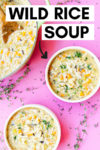 """two bowls of vegan wild rice soup with jackfruit with a dutch oven filled with soup off to the side with a wooden spoon. the array is on a pink background surrounded by thyme sprigs and a text overlay that reads """"wild rice soup"""" with an arrow pointing toward a bowl."""