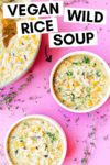 """two bowls of vegan wild rice soup with jackfruit with a dutch oven filled with soup off to the side with a wooden spoon. the array is on a pink background surrounded by thyme sprigs and a text overlay that reads """"vegan wild rice soup"""" with an arrow pointing toward a bowl."""