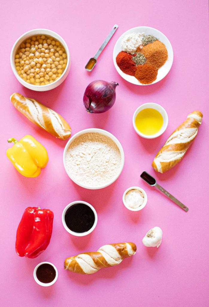 ingredient spread for spicy seitan sausages including vital wheat gluten, spices, garlic, chickpeas, apple cider vinegar, olive oil, liquid smoke, onion, red and yellow bell peppers, molasses, pretzel hot dog buns, vegan mayo, and BBQ sauce